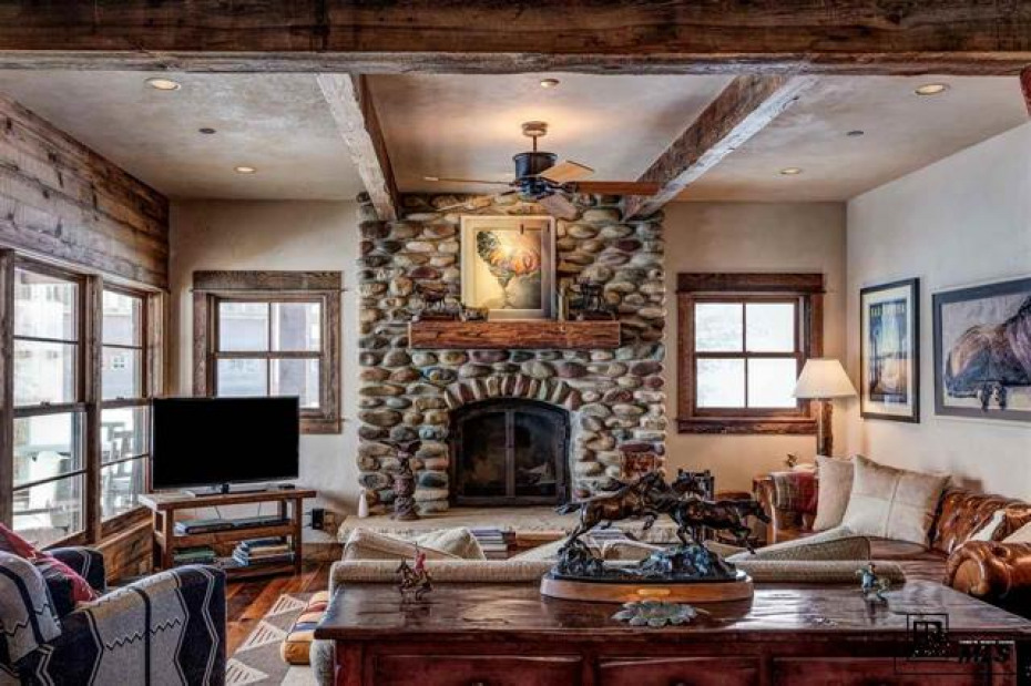 Beautiful river rock fireplace with large windows to enjoy the sunshine. Open and inviting