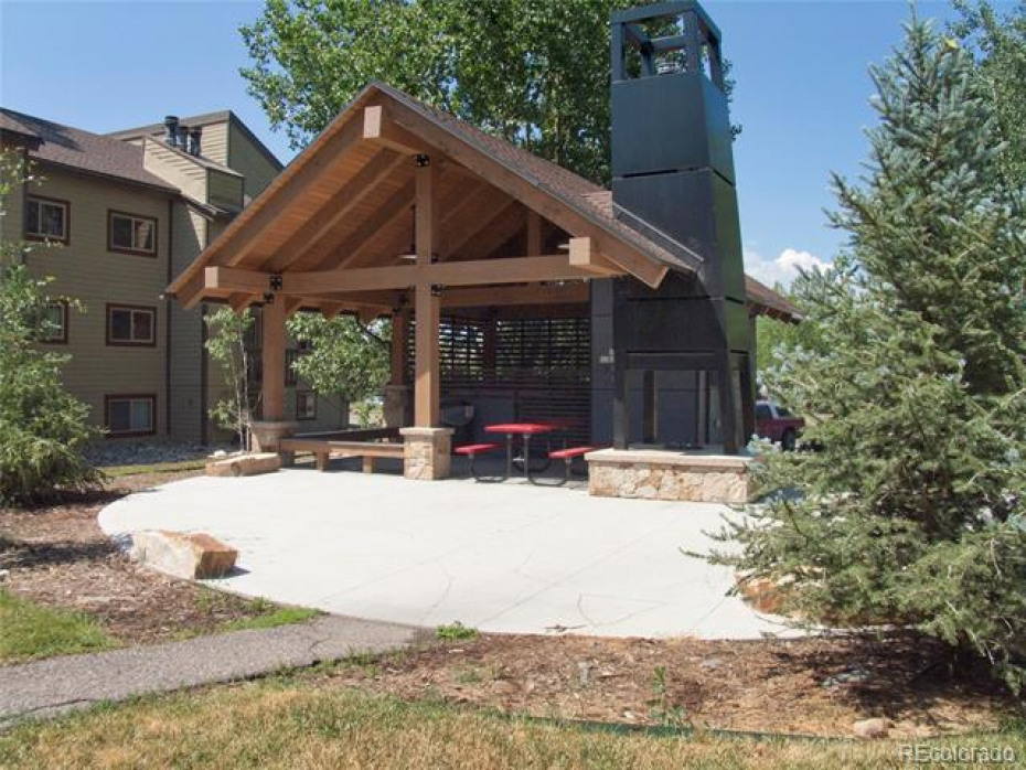 Newer hot tub building with fire pit and community grill and picnic area.