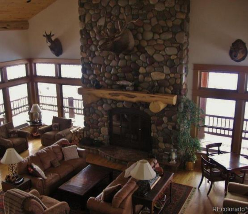 The great room has a massive river rock fireplace and a fully functional bar.