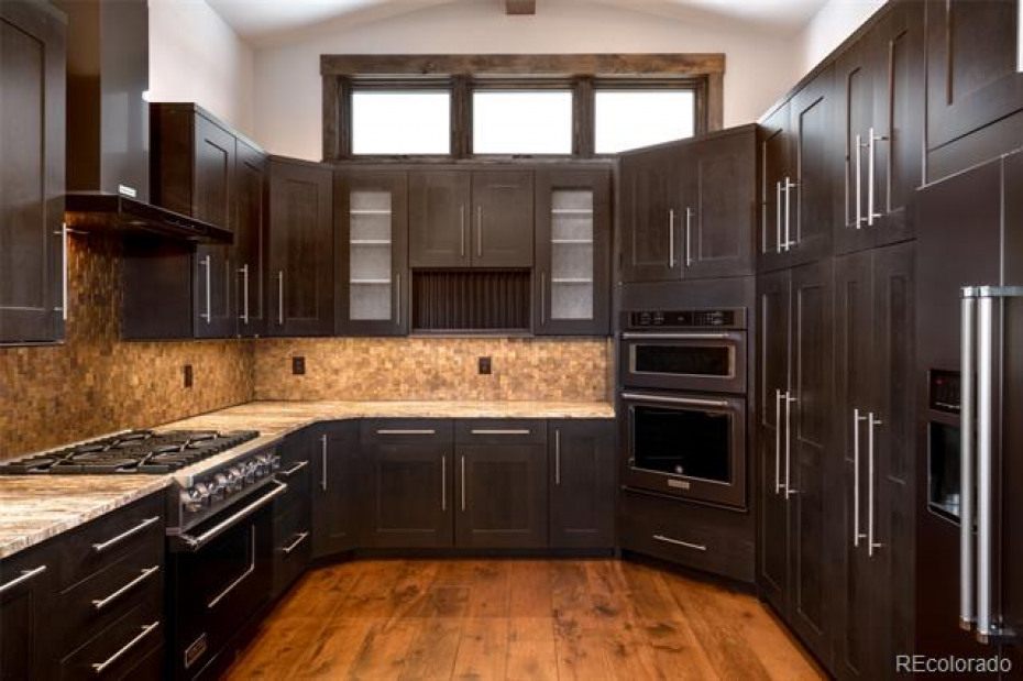 Kitchen with Viking Range, Black Stainless appliances, Cherry cabinets, wide plank Hickory/Pecan wood floors.