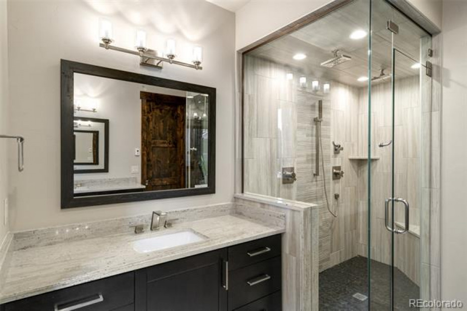 Master bathroom with steam shower.  Shown is one of the floating vanity areas.  The other floating vanity is directly across in the mirror.