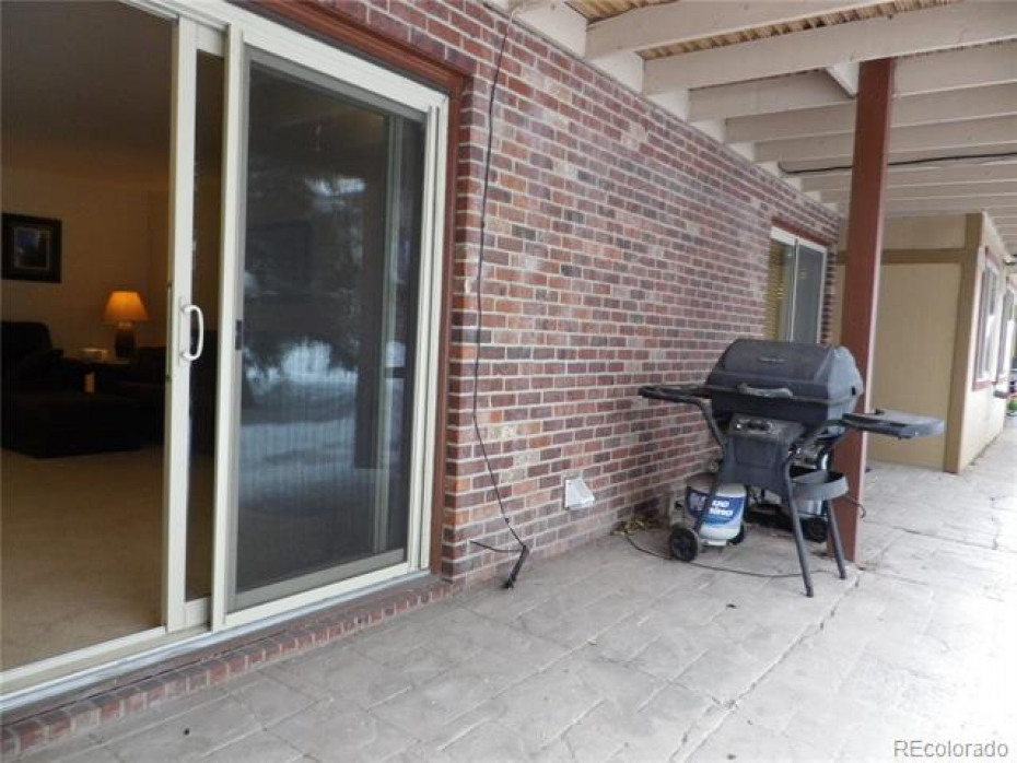 Large sliding glass doors open onto back porch and grill