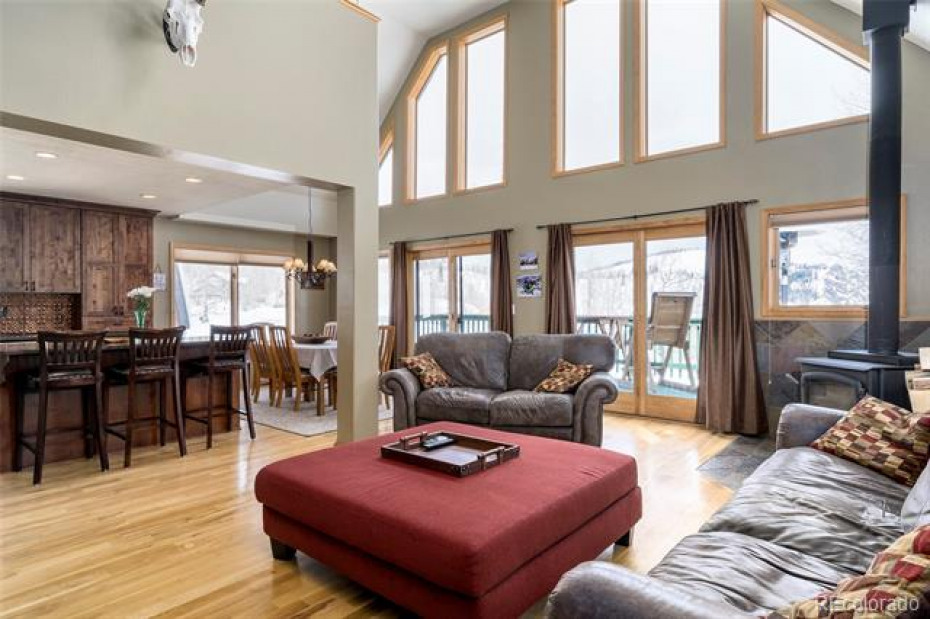 Great room has giant windows and vaulted ceilings