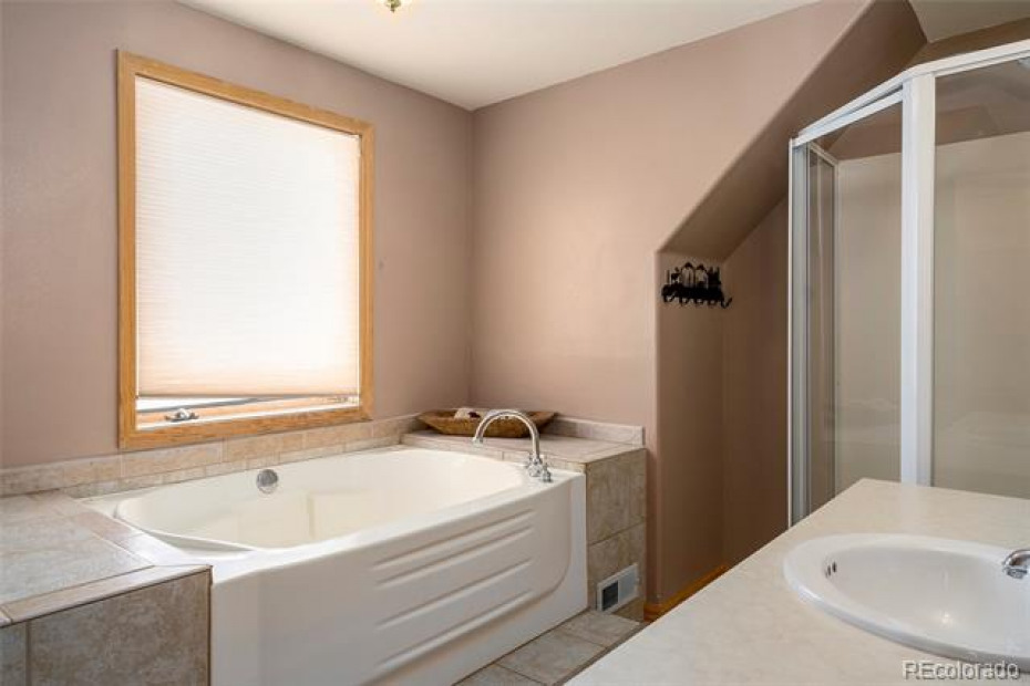 Master suite bathroom has a jetted tub and shower with rain shower head