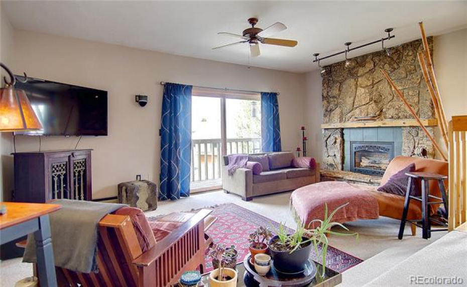 Spacious living room with cozy moss rock gas fireplace and covered deck.