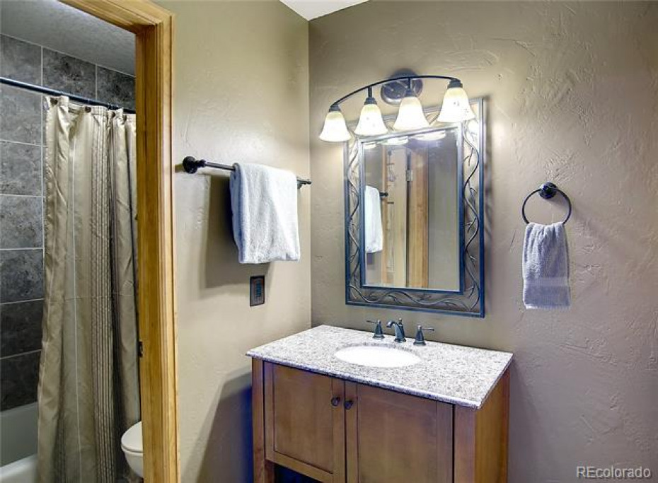 The master bathroom features a granite counter with an undermount sink, brushed nickel fixtures, luxury vinyl flooring and hand troweled wall texture.