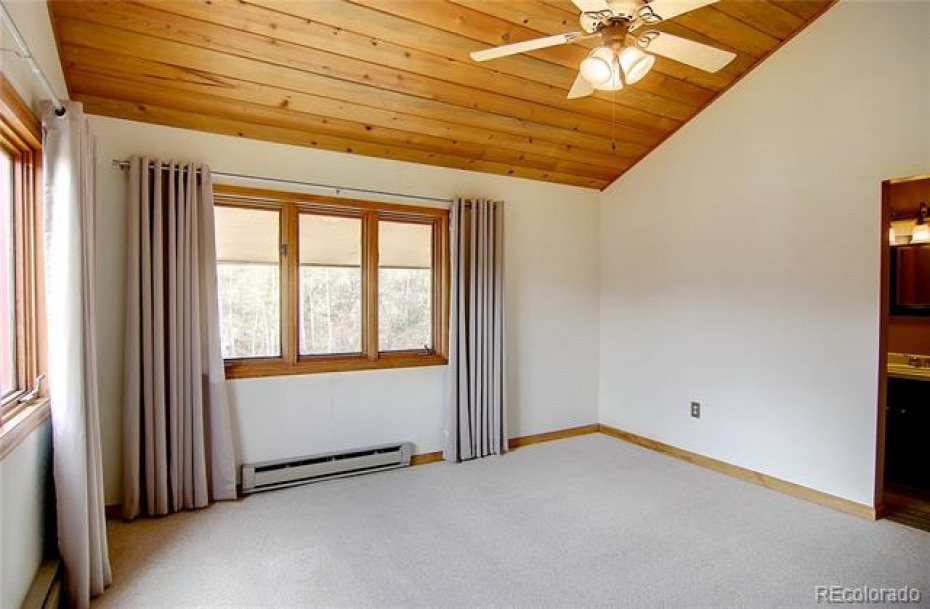 Second bedroom located on upper level with master bedroom, includes en suite bathroom for privacy and convenience.