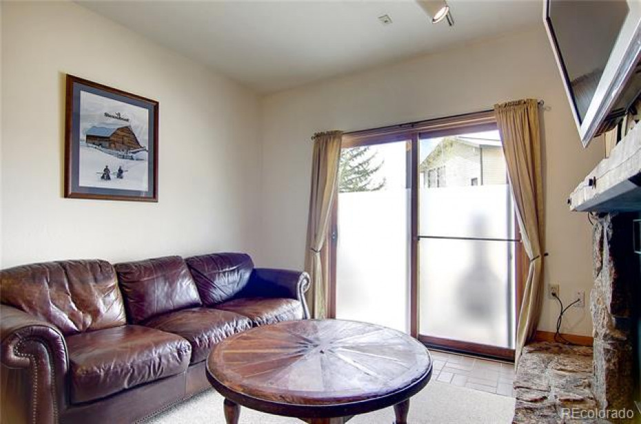 Rec room located on the walkout basement level with a cozy moss rock gas fireplace and private patio!