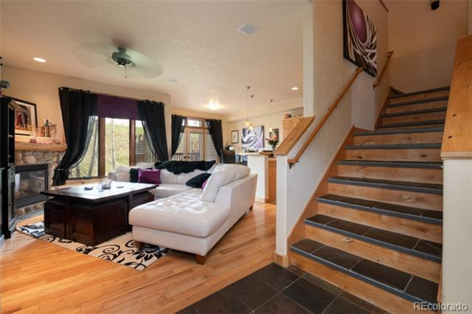 Living area with stairs heading up to Master Bedroom