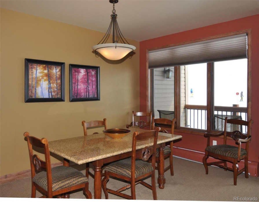 The dining area looks past the covered balcony out onto the ski slopes.
