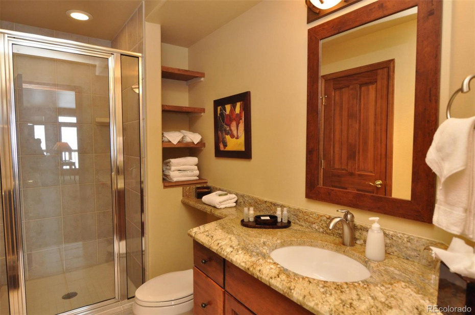 Access to this 3/4 bathroom is through both the living space and the main level bedroom.