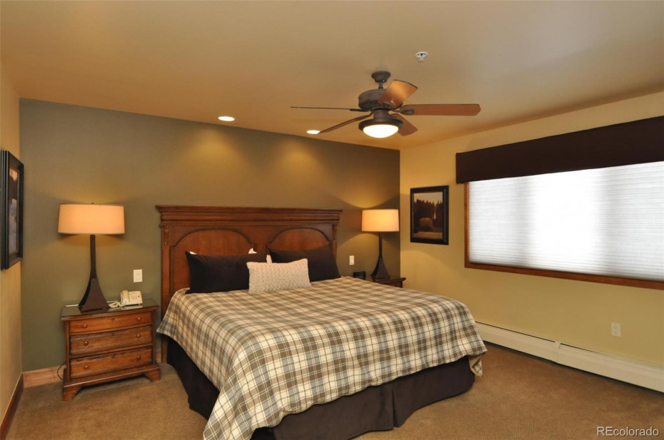 The master bedroom features a king bed and is on the upper level in this floorplan. For the ground level condos, the additional two bedrooms are downstairs.