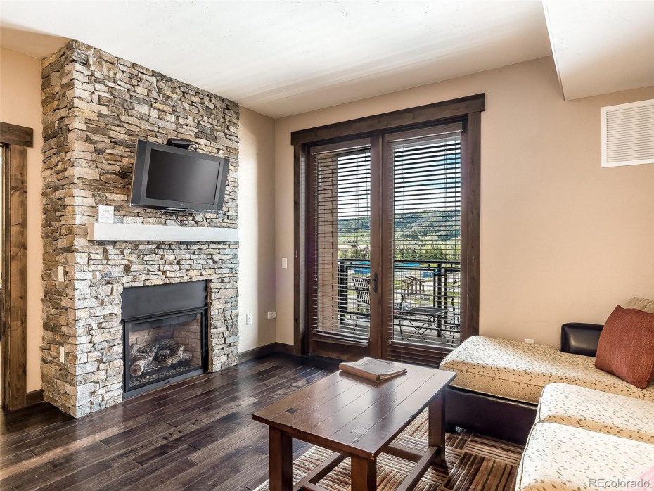 Floor to ceiling natural ledge-stone gas log fireplace.