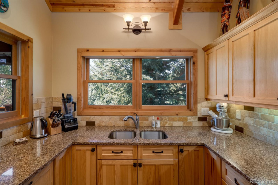 Kitchen with Granite Counter Tops and Bosch Dishwasher with Custom Wood Panel Facade
