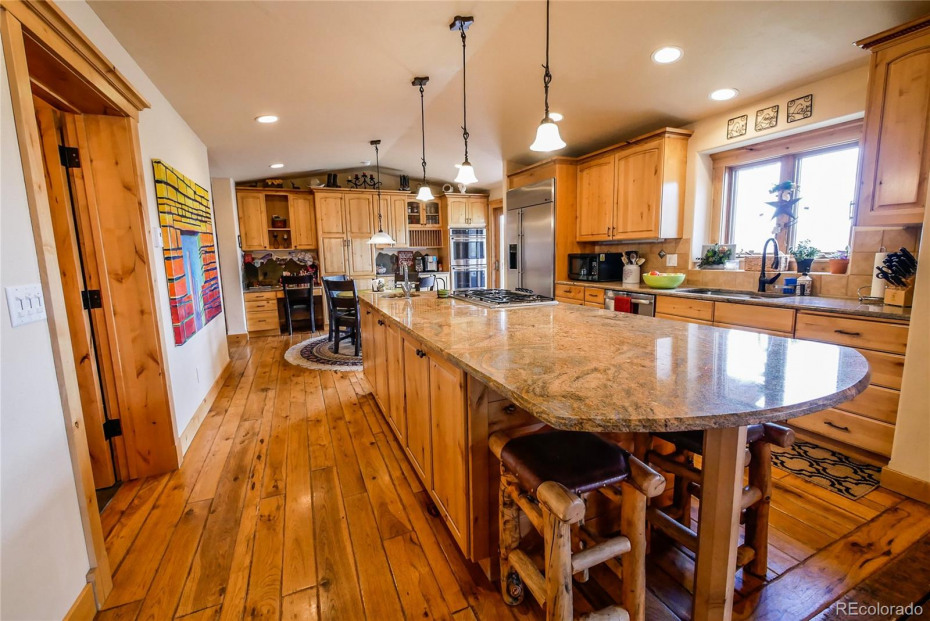 Main Floor Kitchen with Large Granite Island and Top-of-the-Line Appliances