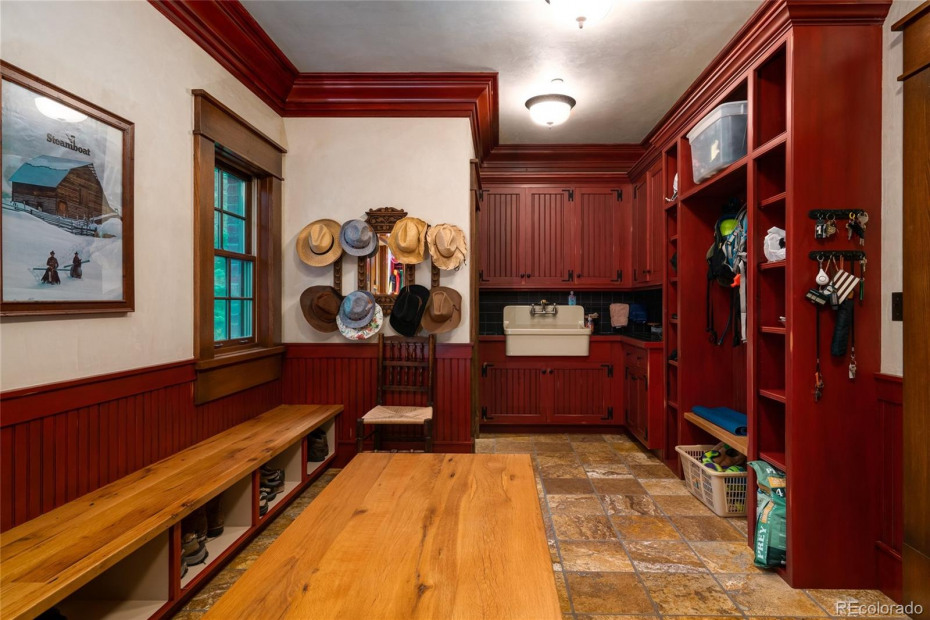 Mud room with ample built-in storage, utility sink, and half bath