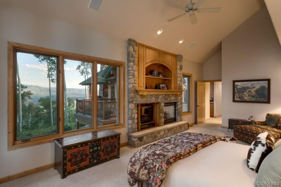Master bedroom with stone fireplace and spectacular views of mountain