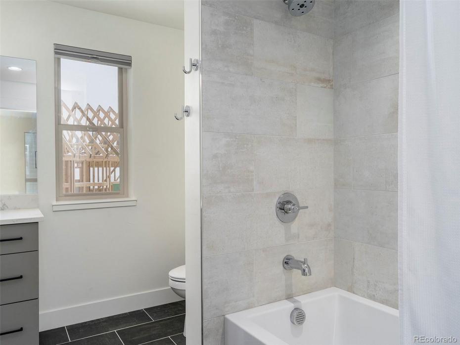 MODEL HOME Bathroom upper level  Floor tile: Black Nickel, Shower tile: Platinum White. Standard plumbing fixtures and glass door (subject to change)