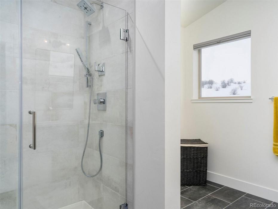 MODEL HOME Master bathroom. Floor tile: Black Nickel, Shower walls tile: Platinum White. Standard plumbing fixtures and glass door (subject to change)