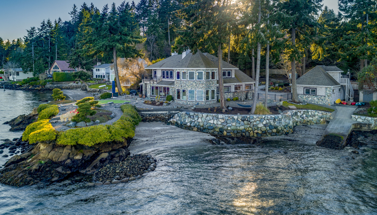 An idyllic waterfront lifestyle and setting with panoramic 240+ degree views, a sandy beach area, and a boat ramp!