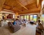 View to the kitchen from the back of the family room! Tall water view windows and French doors to the wraparound deck.