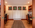 The office off of the family room glass pocket doors, custom built-ins including two work stations.