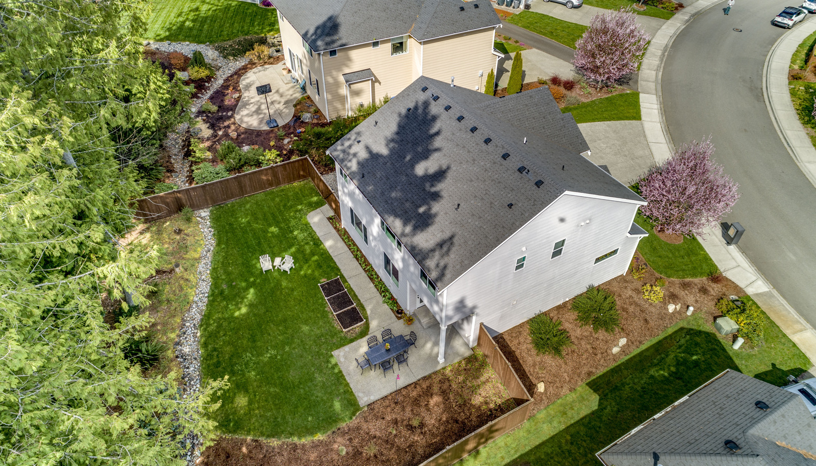 HUGE, private, fully fenced backyard with lush lawn, planter boxes, and your own little forest!