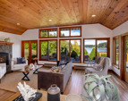 The living room with wood-paneled ceiling, transoms, tall water view windows across the deck and a Fireplace XTRORDINAIR.