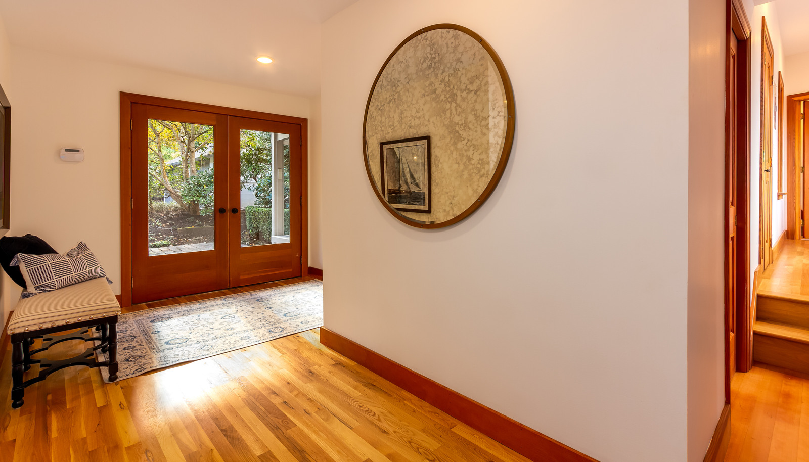 The foyer with French doors and white oak floors. There is a coat closet and powder room upon entry on the left.