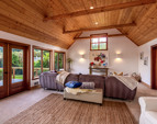 Family room with French doors to the deck, perfect for entertaining; vaulted wood-paneled ceiling and transom!