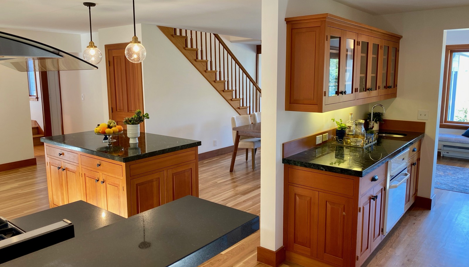 View from the kitchen's breakfast counter to the island, with marble counter and bar with second oven and sink.