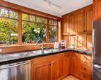 Quality quartz counters, custom cherry cabinetry, Vertical Grain Fir Windows (throughout the entire home) and view to the garden