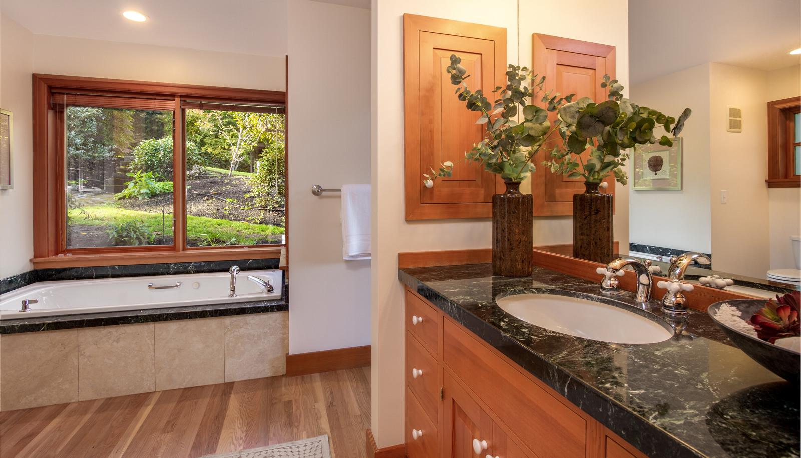 Master bath with jetted soaking tub, hardwood floors, marble vanity.
